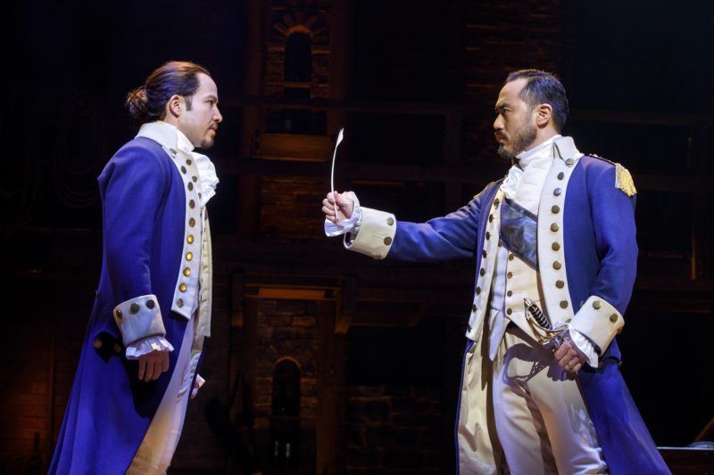 General George Washington hands Alexander Hamilton a quill.